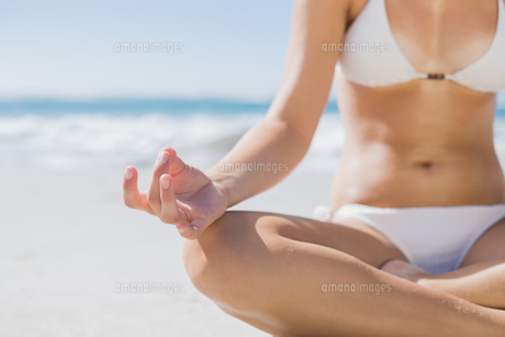 Girl in white bikini sitting in lotus pose on beach FYI00002135
