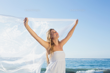 Beautiful calm blonde in white sundress on the beach with scarf FYI00002148