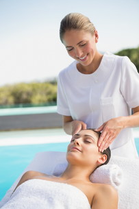 Tranquil brunette getting a head massage poolsideの素材 [FYI00002199]