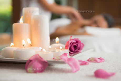Candles and rose petals on massage table FYI00002249