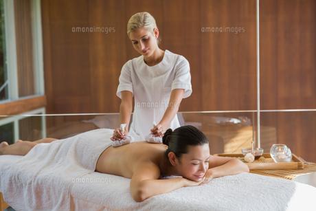 Content brunette enjoying a herbal compress massage FYI00002250