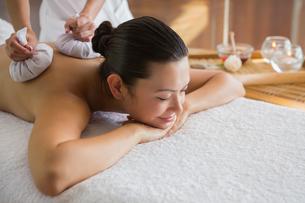 Content brunette enjoying a herbal compress massageの素材 [FYI00002251]