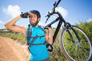 Fit man walking down trail holding mountain bikeの素材 [FYI00002371]