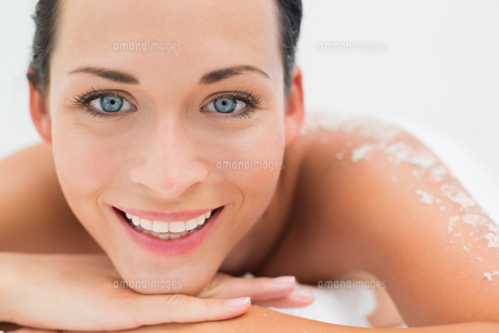 Peaceful brunette lying with salt scrub on back smiling at camera FYI00002442