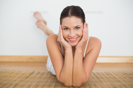 Smiling brunette lying on floor looking at camera FYI00002444