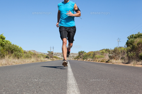 Athletic man jogging on open road FYI00002494