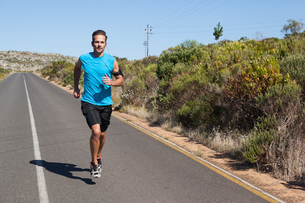 Athletic man jogging on open road FYI00002501