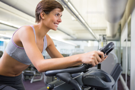 Fit woman working out on the exercise bike FYI00002540
