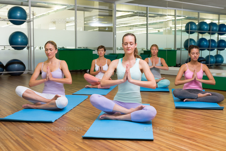 Smiling yoga class in lotus pose in fitness studio FYI00002570