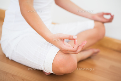 Peaceful woman sitting in lotus pose FYI00002670