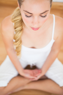 Peaceful blonde sitting in lotus pose FYI00002673