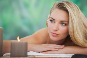 Peaceful blonde lying on towel with candle FYI00002675