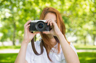 Pretty redhead taking a photo in the park FYI00002686