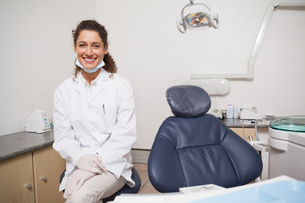 Dentist smiling at camera beside chairの素材 [FYI00002740]