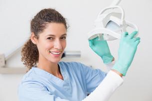 Dentist in blue scrubs smiling at camera beside lightの素材 [FYI00002781]