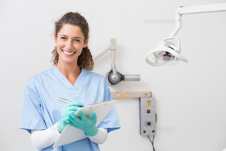 Dentist in blue scrubs writing on clipboardの素材 [FYI00002787]