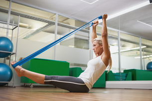 Side view of woman using resistance band in fitness studio FYI00002905