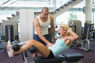 Male trainer assisting woman with abdominal crunches at gym FYI00002915