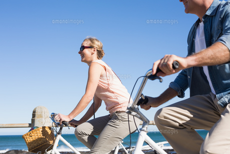 Happy casual couple going for a bike ride on the pier FYI00002999