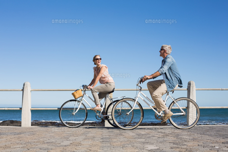 Happy casual couple going for a bike ride on the pier FYI00003004