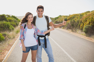 Couple hitchhiking on countryside road FYI00003133