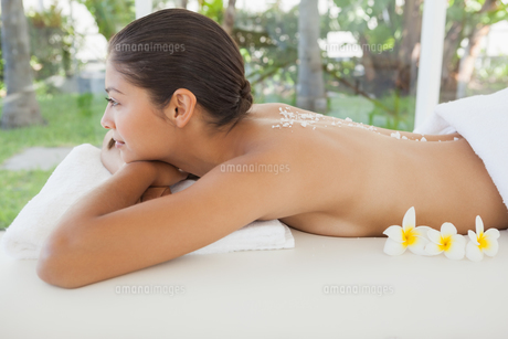 Beautiful brunette relaxing on massage table with salt scrub on back FYI00003234