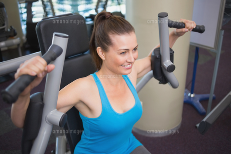 Fit brunette using weights machine for arms FYI00003273