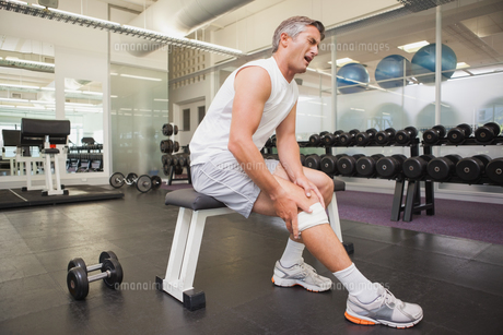 Injured man gripping his knee in the weights room FYI00003313