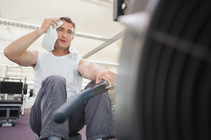Fit man working out on rowing machine FYI00003324