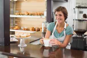 Pretty barista offering cup of coffee smiling FYI00003326