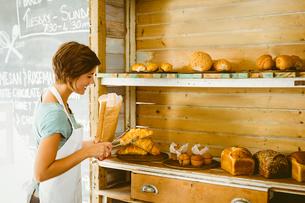 Pretty waitress picking up croissantの素材 [FYI00003329]