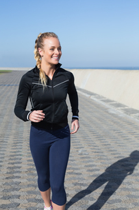 Fit blonde jogging on the pier FYI00003342