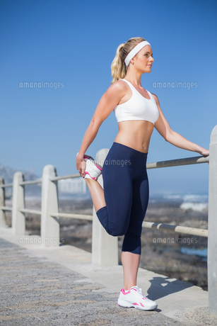 Fit blonde stretching on the pier FYI00003351