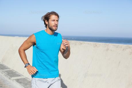 Fit man jogging on promenade FYI00003399