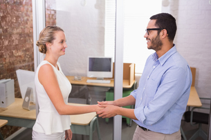 Executives shaking hands in office FYI00003454
