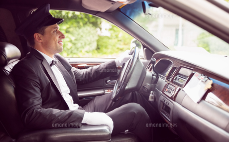 Limousine driver driving and smiling FYI00003512