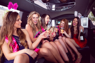 Happy friends drinking champagne in limousine FYI00003514