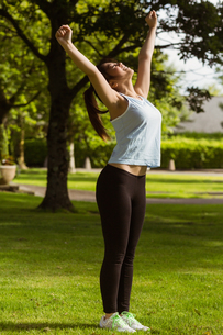 Side view of healthy woman stretching hands in park FYI00003560