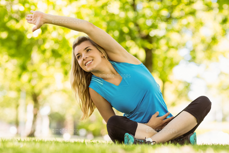 Fit blonde stretching in the park FYI00003615