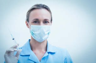 Female dentist in surgical mask holding injectionの素材 [FYI00003640]