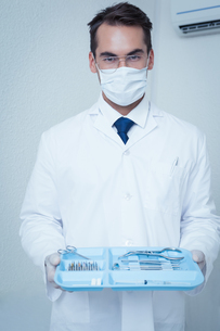 Male dentist in surgical mask holding tray of toolsの素材 [FYI00003657]