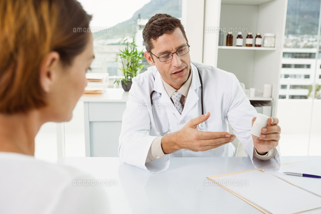Doctor giving prescription to patient in medical office FYI00003762