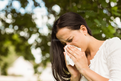 Sick brunette blowing her nose FYI00003831
