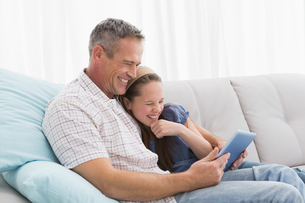 Father with daughter relaxing on the couch using laptop FYI00004000