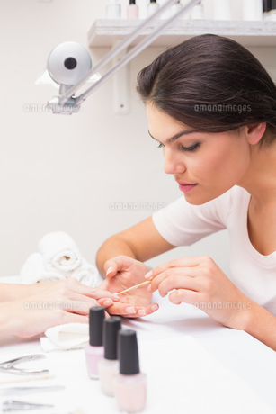 Nail technician giving customer a manicure FYI00004175