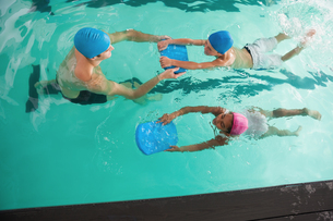 Cute swimming class in pool with coach FYI00004366
