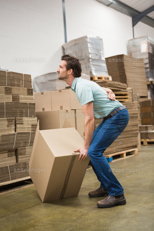 Worker with backache while lifting box in warehouse FYI00005008
