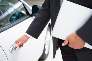 Man holding a car door handles while holding clipboard FYI00005220