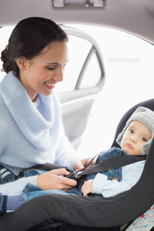 Mother securing her baby in the car seat FYI00005296