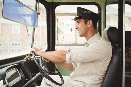 Smiling driver driving the school bus FYI00005510